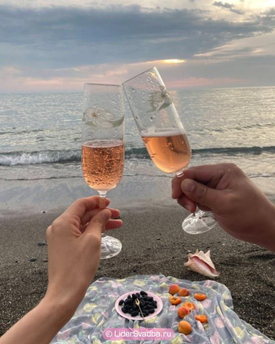 жених и невеста опускают одну жемчужину в бокал с шампанским